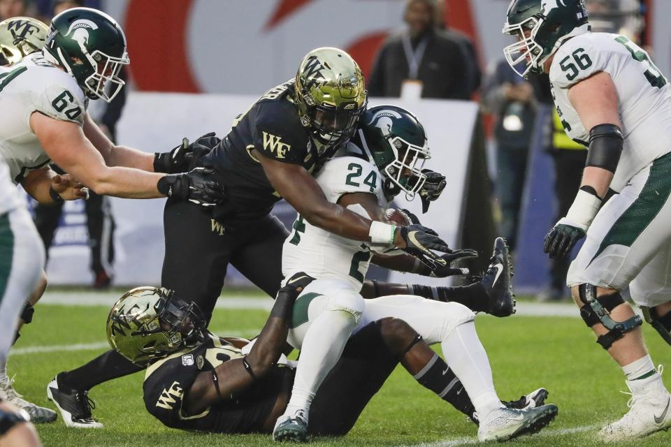 Wake Forest's Tayvon Bowers, centerleft, and Ja'Cquez Williams, bottom, tackle Michigan State's Elijah Collins (24) during the first half of the Pinstripe Bowl NCAA college football game Friday, Dec. 27, 2019, in New York. (AP Photo/Frank Franklin II)