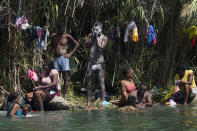 Haitian migrants bathe and do laundry along the banks of the Rio Grand after they crossed into the United States from Mexico, Saturday, Sept. 18, 2021, in Del Rio, Texas. (AP Photo/Eric Gay)