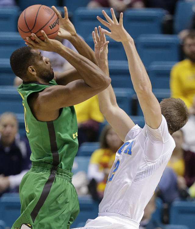 Oregon's Mike Moser, left, shoots against UCLA's David Wear in the first half of an NCAA Pac-12 conference tournament quarterfinal college basketball game on Thursday, March 13, 2014, in Las Vegas. (AP Photo/Julie Jacobson)