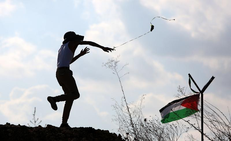 A protester hurls a stone next to a Palestinian flag during clashes with Israeli security forces in the West Bank town of Tulkarem on November 10, 2015 (AFP Photo/Jaafar Ashityeh)