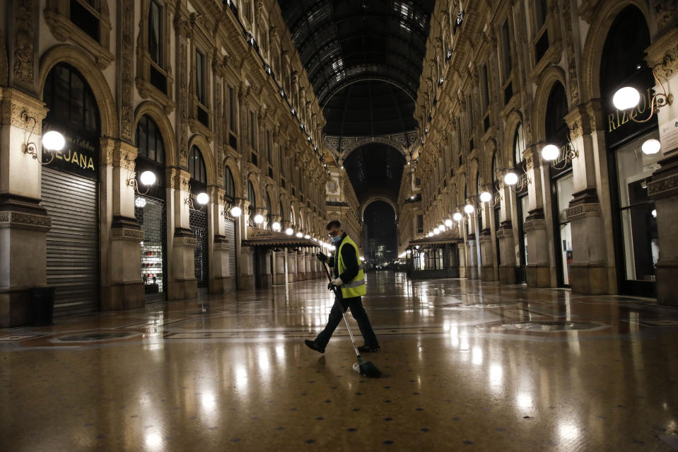 A cleaner sweeps in an empty Vittorio Emanuele II arcarde, in Milan, northern Italy, early Sunday, Oct. 25, 2020. Since the 11 p.m.-5 a.m. curfew took effect last Thursday, people can only move around during those hours for reasons of work, health or necessity. (AP Photo/Luca Bruno)