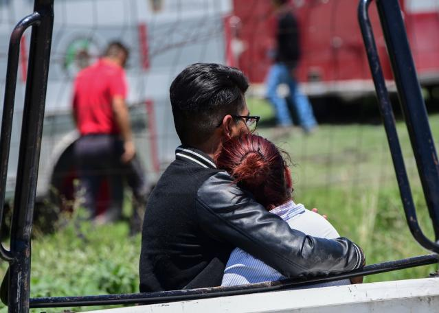 <p>A man and woman embrace as they look at the site of a series of explosions at fireworks warehouses in Tultepec, central Mexico, on July 5, 2018. – At least 17 people were killed, including rescue workers who died saving others' lives, officials said. The initial explosion occurred around 9:30 am (1430 GMT), then spread to other warehouses just as police and firefighters began attending to the first victims. (Photo: Pedro Pardo/AFP/Getty Images) </p>