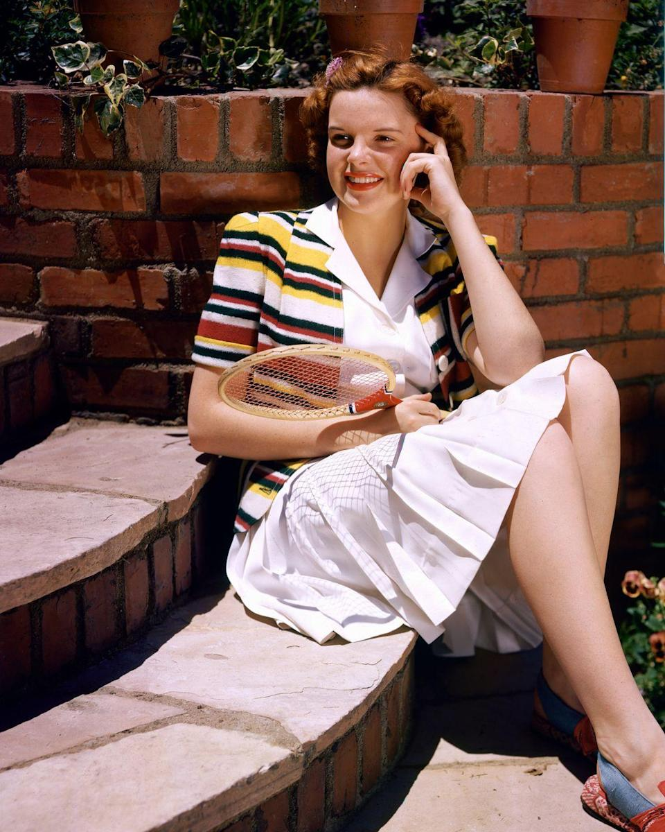 <p>Judy Garland looks ready for a match up as she poses with a badminton racket in her backyard in 1945.</p>