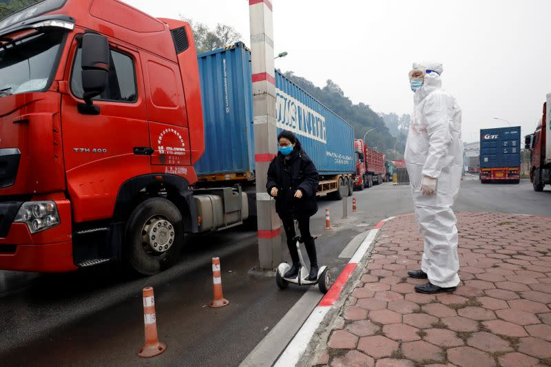 A Vietnamese health worker looks on as a Chinese trader in protective mask rides a hoverboard along container trucks going from China to Vietnam, at Huu Nghi border gate connecting with China, in Lang Son province, Vietnam