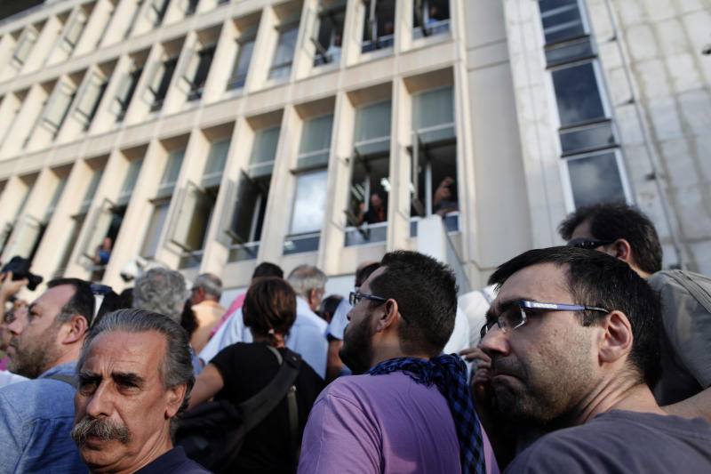 People stand in front of the Greek state television ERT headquarters after the government's announcement that it will shut down the broadcaster in Athens, on Tuesday, June 11, 2013. Greece is to close down all its state-run TV and radio stations with the loss of some 2,500 jobs as part of its cost-cutting drive demanded by the bailed-out country's international creditors. Tuesday's move heralds the first direct public sector layoffs in more than three years of painful austerity, which have cost about a million private sector jobs. (AP Photo/Petros Giannakouris)