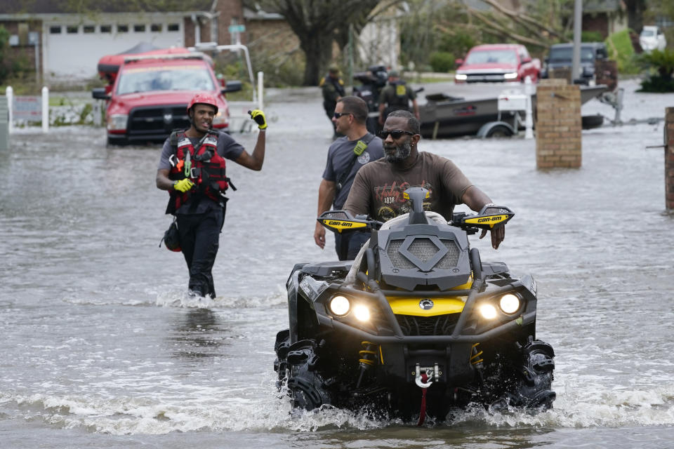 A resident of the Spring Meadow subdivision drives a four wheeler out of flood waters followed by rescue personnel after Hurricane Ida moved through Monday, Aug. 30, 2021, in LaPlace, La. (AP Photo/Steve Helber)