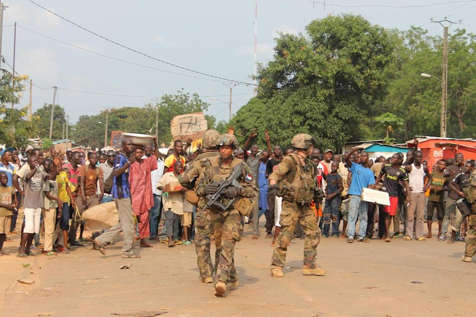"""People demonstrate in front of French soldiers of the """"Sangaris Operation"""" to protest against a disarmament operation of anti-balakas militias within the area, on June 23, 2014 in Bimbo near Bangui (AFP Photo/Pacome Pabandji)"""