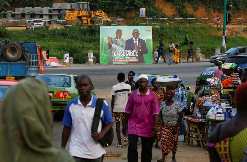 People walk pass next to a campaign billboard showing the candidats of the ruling coalition party, the Rally of Houphouetists for Democracy and Peace (RHDP) ahead of the legislative election in Abidjan