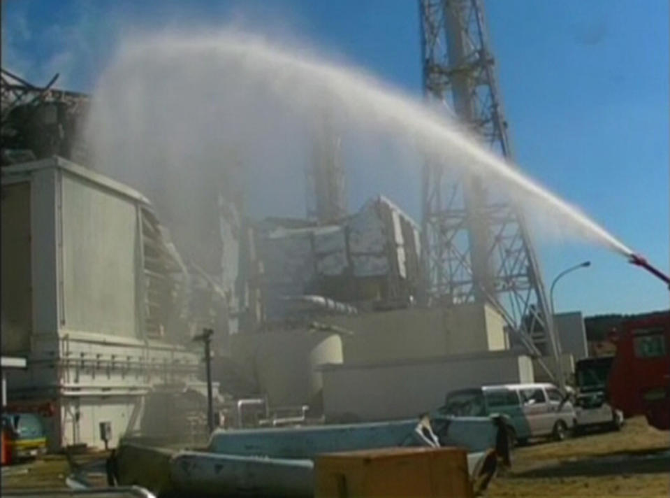 <p>FILE PHOTO: A fire truck sprays water at No. 3 reactor of the Fukushima Daiichi nuclear power plant in Tomioka, Fukushima prefecture in this still image taken from a video by the Self Defence Force Nuclear Biological Chemical Weapon Defense Unit on March 18, 2011. REUTERS/Self Defence Force Nuclear Biological Chemical Weapon Defense Unit via Reuters TV</p>