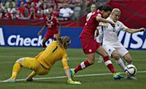 Canada's Christine Sinclair (C) pushes between England goalkeeper Karen Bardsley (L) and defender Laura Bassett to score during the match at the 2015 FIFA Women's World Cup at BC Place Stadium in Vancouver on June 27, 2015 (AFP Photo/Andy Clark)