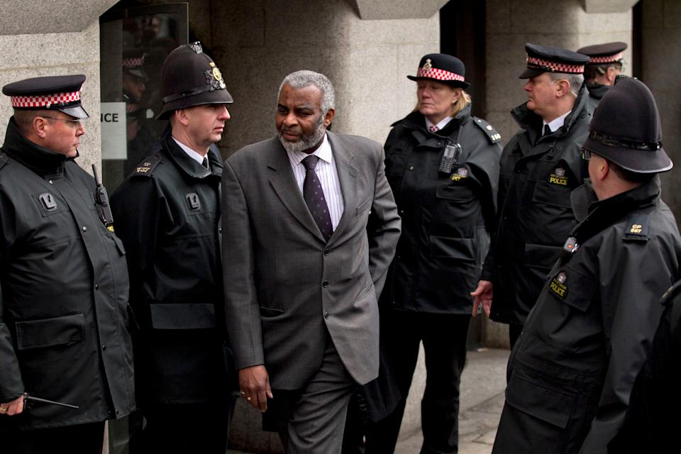 Neville Lawrence, centre, the father of murdered black teenager Stephen Lawrence, walks through police officers to speak to the media outside the Old Bailrey after Gary Dobson and David Norris were sentenced for their part in the murder (Photo: ASSOCIATED PRESS)