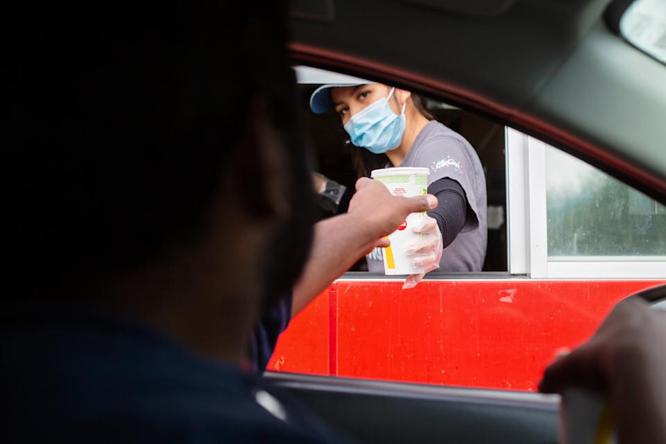 Prince Rupert, Canada - May 17, 2020. A man reaches for his food at the McDonalds drive-thru window as the employee wears a mask for protection.