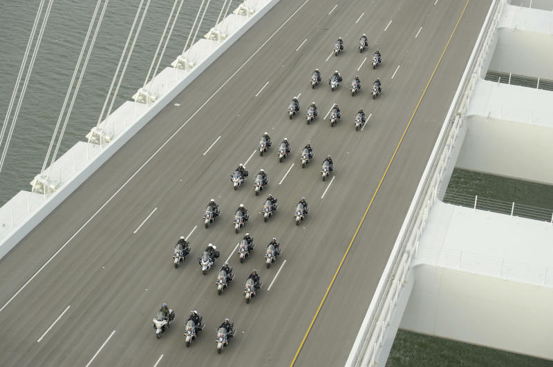 In this photo taken on Monday, Sept. 2, 2013, provided by the Bay Area Toll Authority, a phalanx of police officers lead a procession across the San Francisco-Oakland Bay Bridge to mark the east span's opening in San Francisco. At the modest inaugural ceremony, the new, self-anchored suspension bridge with its looming, single white tower was praised as a dramatic safety upgrade over its predecessor. It also was held up as a beautiful example of public art. (AP Photo/Bay Area Toll Authority, Noah Berger ) MAGS OUT, NO SALES