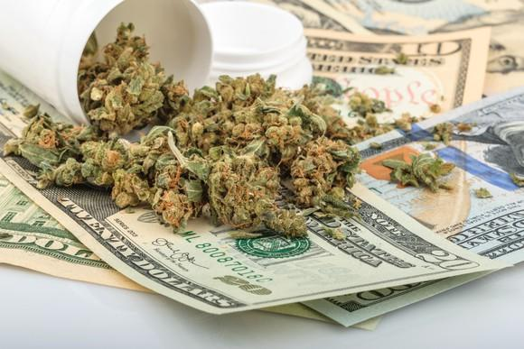 A tipped over bottle filled with dried cannabis lying on a messy pile of cash bills.