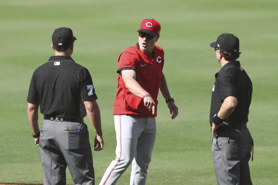 Cincinnati Reds manager David Bell, center, argues with umpires Jim Reynolds, left, and Chris Guccione, right, after Joey Votto was called out on a checked swing in the first inning of a baseball game against the San Diego Padres, Saturday, June 19, 2021, in San Diego. (AP Photo/Derrick Tuskan)