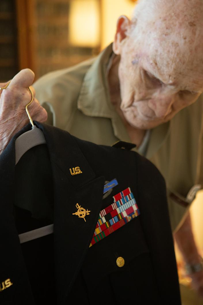 """Holding up his retired uniform, Crosby """"Bing"""" Powell, 96, talks about his time serving in the U.S. Army during World War II. The current owner of Powell's former home, Mikell Burr, found some of Powell's war medals and memorabilia in the loft above her garage when she was cleaning it out over the Labor Day weekend."""