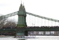 FILE PHOTO: Spectators crowd Hammersmith Bridge to watch Oxford University's 8 pull past Cambridge's rowing team in the Boat Race on the River Thames in London