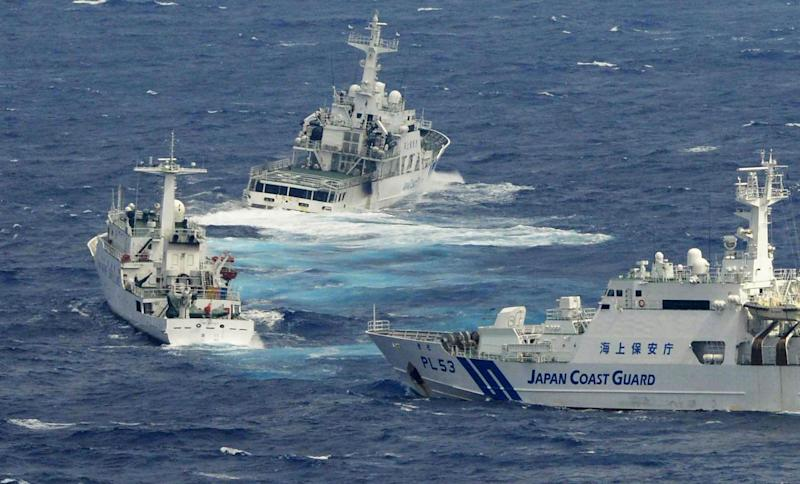 FILE - In this Sept. 24, 2012 file photo, Japan Coast Guard vessels, right, and rear, sail along with Chinese surveillance ship Haijian No. 66, left, near disputed islands, called Senkaku in Japan and Diaoyu in China, in the East China Sea. Chinese patrol boats have harried the Japanese Coast Guard many times a week for more than a month in an unusually relentless response to their latest maritime spat. China says ships from its Marine Surveillance service are merely defending Chinese sovereignty and protesting illegal Japanese control over the uninhabited islands, known as Senkaku in Japan and Diaoyu in China. (AP Photo/Kyodo News, File) JAPAN OUT, MANDATORY CREDIT, NO LICENSING IN CHINA, HONG KONG, JAPAN, SOUTH KOREA AND FRANCE