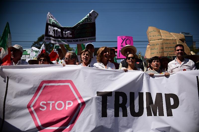 People hold sugns against US President Donald Trump during an anti-Trump march in Mexico City, on February 12, 2017
