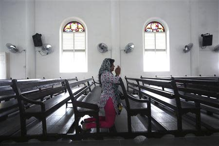 "A woman prays inside the church of Our Lady of Lourdes at Klang, outside Kuala Lumpur January 12, 2014. The Sunday Mass at Our Lady of Lourdes Catholic church seems like a model for the multicultural, tolerant Malaysia that its government likes to present to the outside world. A long tussle over who can say ""Allah"" in Malaysia has flared anew, as Islamization that many see as driven by political forces threatens to erode the secular constitution and minority rights in the ethnically diverse country following a divisive election last year. Picture taken January 12, 2014. To march Feature RELGION-MALAYSIA/ REUTERS/Samsul Said"