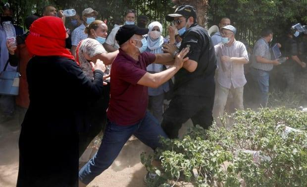 A supporter of Tunisia's biggest political party, the Islamist Ennahda, scuffles with a police officer near the parliament building in Tunis on July 26. (Zoubeir Souissi/Reuters - image credit)