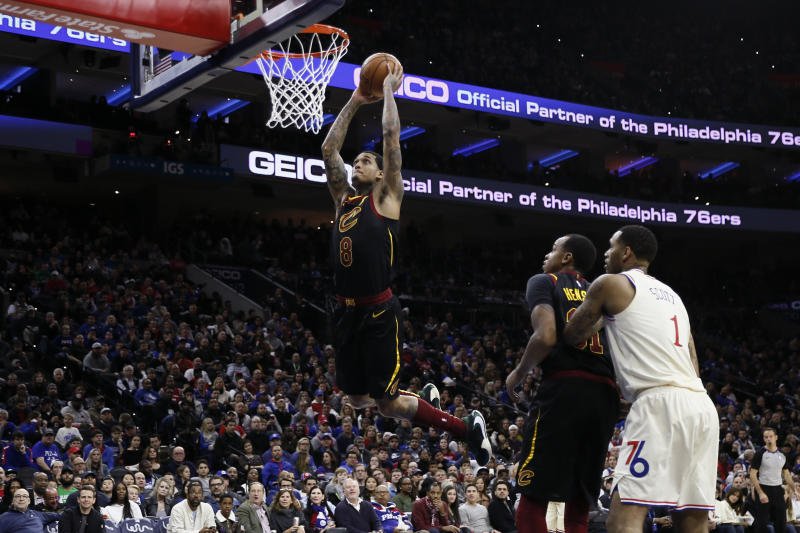 Cleveland Cavaliers' Jordan Clarkson (8) goes up for a dunk as Philadelphia 76ers' Mike Scott (1) and Cavaliers' John Henson (31) look on during the second half of an NBA basketball game, Saturday, Dec. 7, 2019, in Philadelphia. (AP Photo/Matt Slocum)