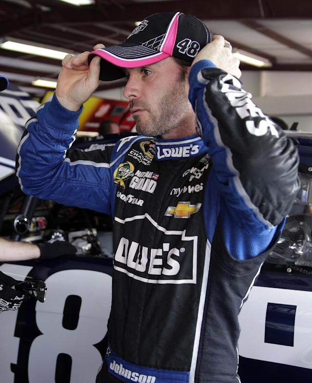 Driver Jimmie Johnson adjusts his hat after climbing out of his car during practice for Sunday's NASCAR Sprint Cup Series auto race at Talladega Superspeedway in Talladega, Ala., Friday, Oct. 18, 2013.(AP Photo/Jay Sailors)
