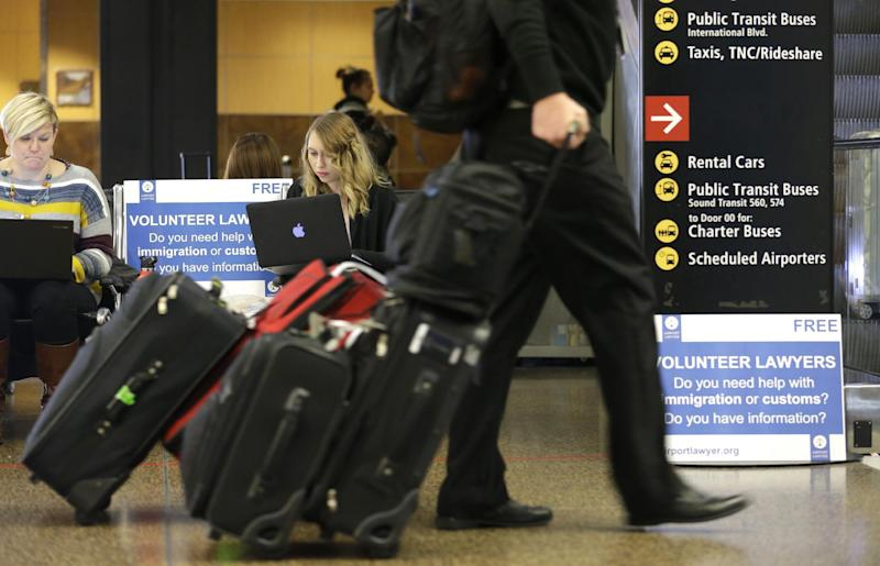 Asti Gallina, center, a volunteer law student from the University of Washington, works at a station near where passengers arrive on international flights at Seattle-Tacoma International Airport Tuesday, Feb. 28, 2017, in Seattle. Gallina was volunteering with the group Airport Lawyer, which also offers a secure website and mobile phone app that alerts volunteer lawyers to ensure travelers make it through customs without trouble. Airport officials and civil rights lawyers around the country are getting ready for President Donald Trump's new travel ban, which is expected to be released as soon as Wednesday. (AP Photo/Ted S. Warren)