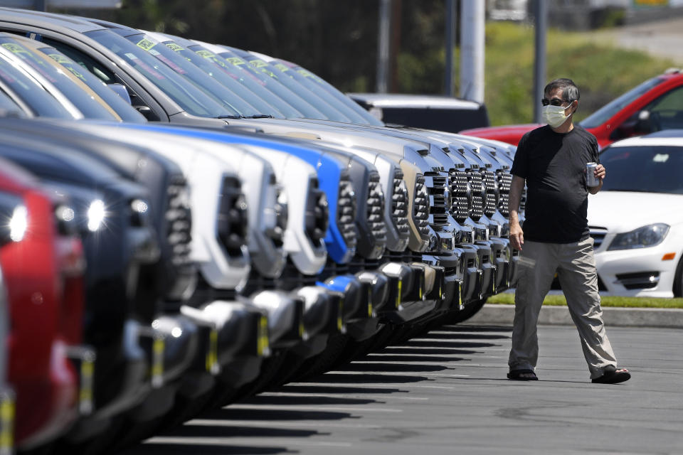A customer looks at trucks at Longo Toyota during the coronavirus outbreak, Friday, May 8, 2020, in El Monte, Calif. Longo claims to be the largest car dealership in the world with over 3,000 cars in stock. California Gov. Gavin Newsom has issued the broadest loosening of his stay-at-home order so far, allowing some retailers to reopen. (AP Photo/Mark J. Terrill)