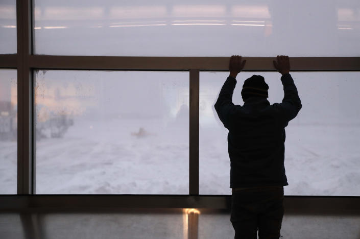 <p>A stranded traveler watches front loaders clear snow from the apron around Gates C and D at Terminal B at LaGuardia Airport, Thursday, Jan. 4, 2018, in New York. (Photo: Julie Jacobson/AP) </p>