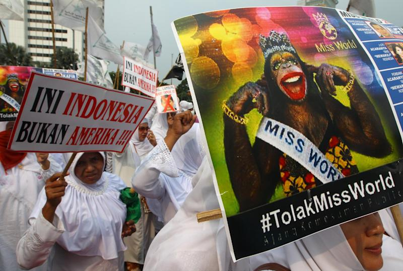 In this Friday, Sept. 6, 2013 photo, Muslim women hold posters reading: Indonesia is not America, left, and Reject Miss World, during a protest demanding the cancellation of the Miss World pageant, in Jakarta, Indonesia. Beauty queens and backstage drama may seem inevitable, but at this year's Miss World competition, something more serious than hair-pulling and name-calling has come from host country Indonesia: Muslim hardliners have threatened to hijack the competition despite major concessions from the government and organizers. (AP Photo/Dita Alangkara)