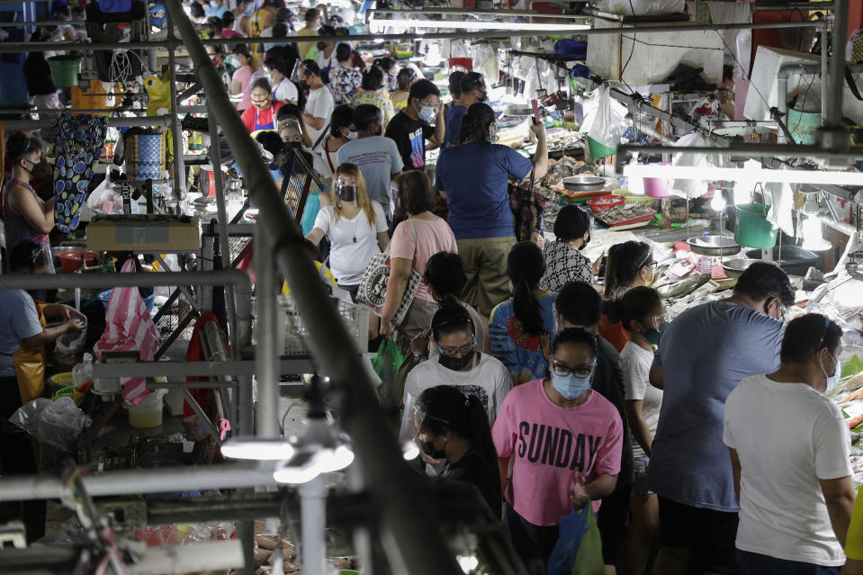 People wearing face masks and face shields to prevent the spread of the coronavirus buy food at the Munoz market in Quezon city, Philippines as they prepare for a stricter lockdown on Sunday March 28, 2021. The government will start stricter lockdown measures next week as the country struggles to control an alarming surge in COVID-19 cases. (AP Photo/Aaron Favila)
