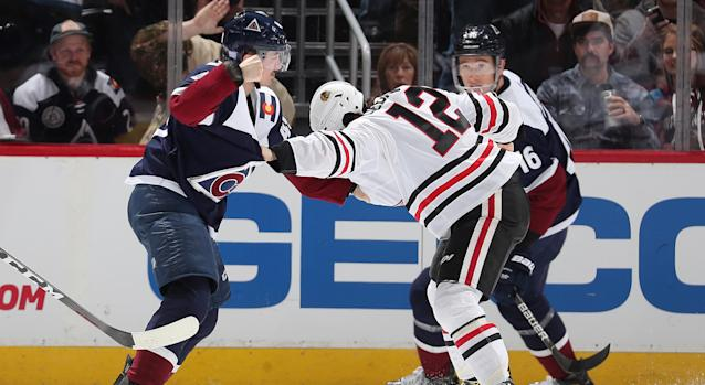 Samuel Girard of the Colorado Avalanche (left) throws hands with Alex DeBrincat of the Chicago Blackhawks at the Pepsi Center on Saturday night. (Photo by Michael Martin/NHLI via Getty Images)