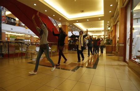 Shoppers and shop assistants raise their hands as they are escorted to safety while armed police hunt gunmen who went on a shooting spree in Westgate shopping centre in Nairobi September 21, 2013. REUTERS/Goran Tomasevic