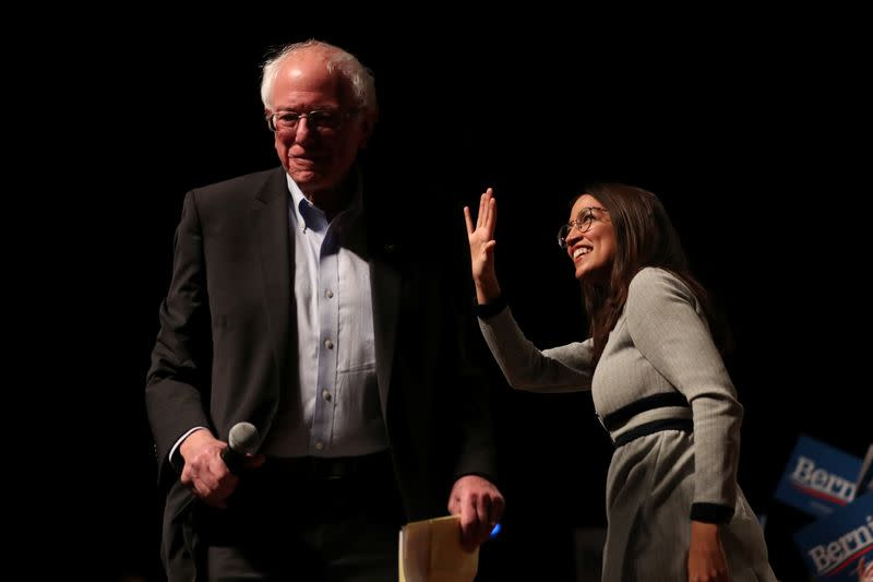 Democratic 2020 U.S. presidential candidate arrives at a campaign rally while Rep. Alexandria Ocasio-Cortez waves in Ames, Iowa