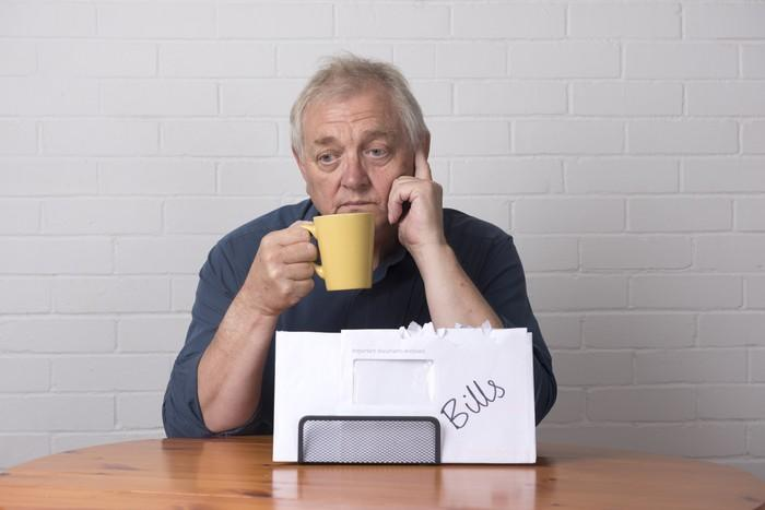 A visibly concerned senior man holding a mug in his right hand with a pile of bills in front of him.