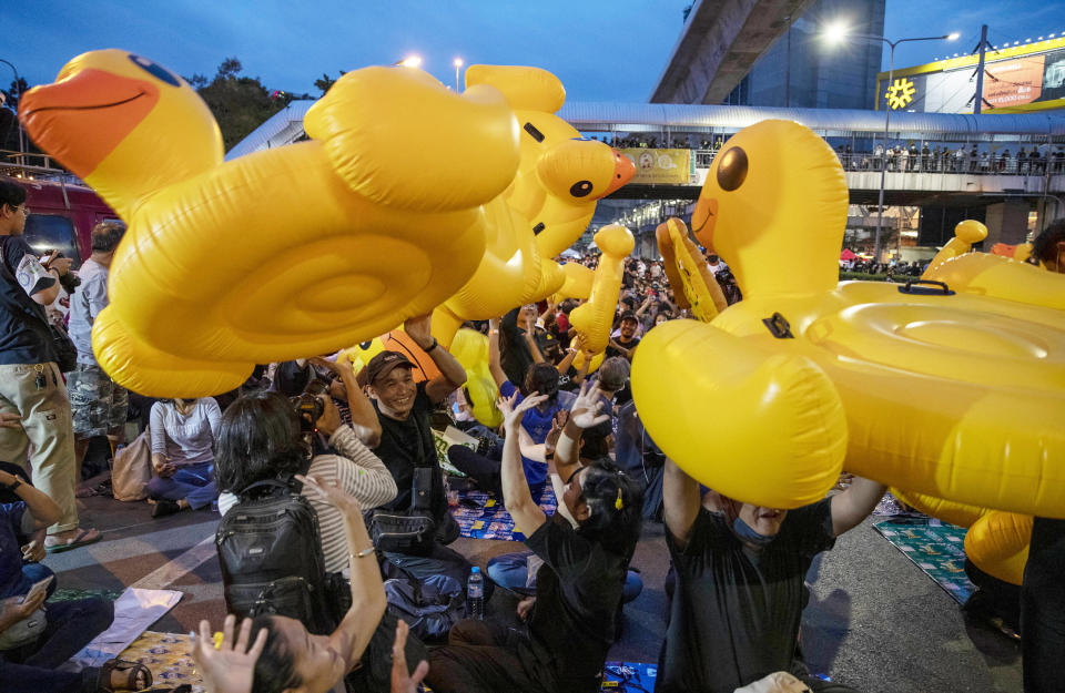 Inflatable yellow ducks, a current symbol of the protest movement, are lifted over a crowd of anti-government protesters attending a rally Wednesday, Dec. 2, 2020, in Bangkok, Thailand. Thailand's highest court Wednesday acquitted Prime Minister Prayuth Chan-ocha of breaching ethics clauses in the country's constitution, allowing him to stay in his job. (AP Photo/Gemunu Amarasinghe)