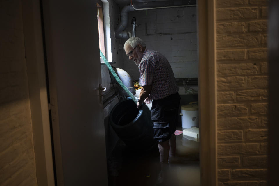 Wiel de Bie pumps water out of his flooded basement, in the town of Brommelen, Netherlands, Saturday, July 17, 2021. In the southern Dutch province of Limburg, which also has been hit hard by flooding, troops piled sandbags to strengthen a 1.1-kilometer (0.7 mile) stretch of dike along the Maas River, and police helped evacuate low-lying neighborhoods. (AP Photo/Bram Janssen)