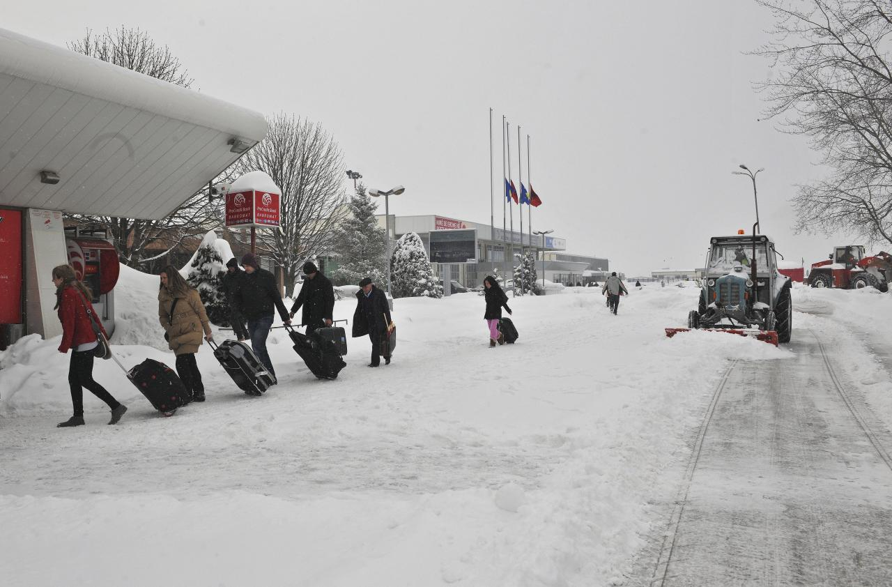 Passengers pull bags through snow after flights were canceled in Kosovo's main airport in Slatina on Monday, Feb. 13, 2012. Low temperatures and heavy snowfall has engulfed Kosovo for a month causing delays in traffic and forcing authorities to suspend school. Europe has been battling a deep freeze that started in late January. ( AP Photo / Visar Kryeziu )