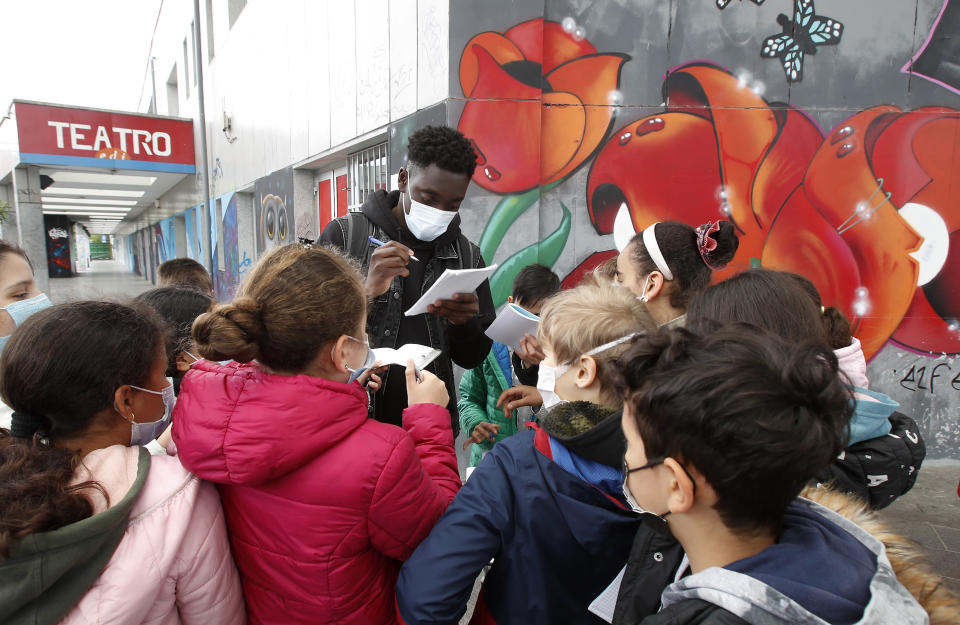 """Actor Giuseppe Dave Seke signs autographs to children, in Milan, Italy, Tuesday, April 27, 2021. The Netflix series """"Zero,"""" which premiered globally last month, is the first Italian TV production to feature a predominantly black cast, a bright spot in an otherwise bleak television landscape where the persistent use of racist language and imagery in Italy is sparking new protests. (AP Photo/Antonio Calanni)"""