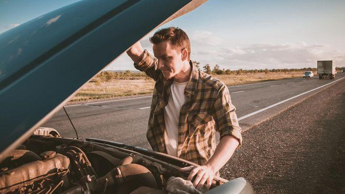 man with broken down car on highway