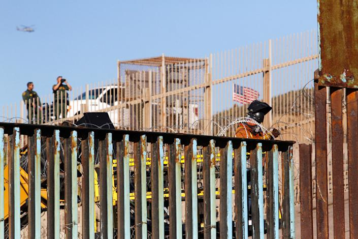<p>U.S. border patrol look out as a welder reinforces the border fence between Mexico and the United States with concertina wire, in Tijuana, Mexico, Nov. 14, 2018. (Photo: Jorge Duenes/Reuters) </p>