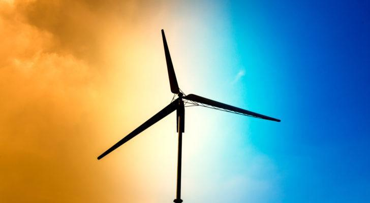 A wind turbine appears in silhouette against a bright orange and blue sky.