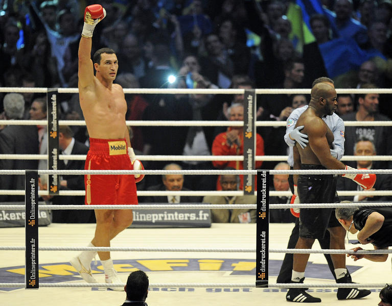 Heavyweight world boxing champion Wladimir Klitschko of Ukraine, left, celebrates after knocking out knock Jean-Marc Mormeck of France, right, in the fourth round of their WBA, IBF, WBO and IBO title bout in Duesseldorf, Germany, Saturday, March 3, 2012. (AP Photo/Martin Meissner)
