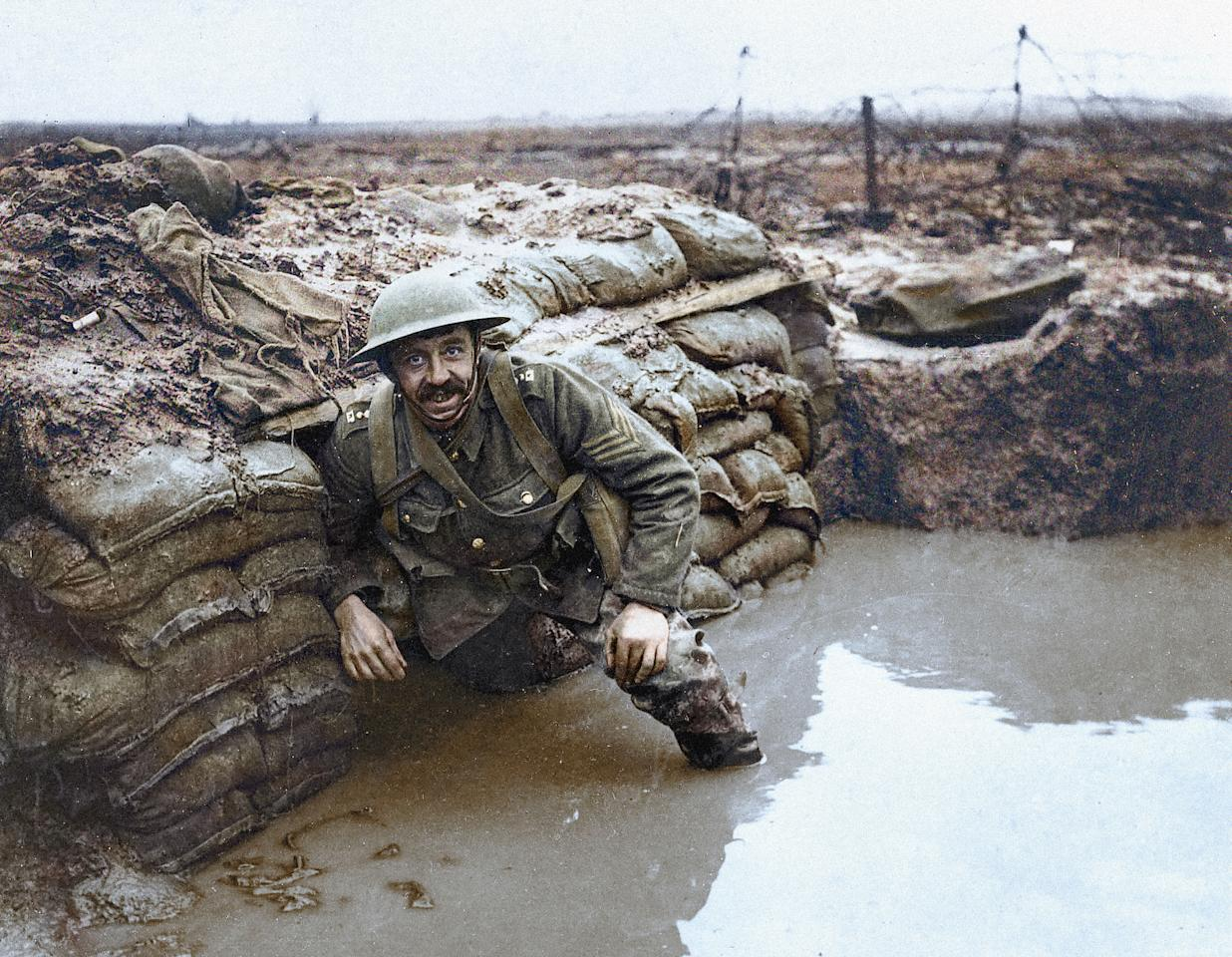 <p>A British sergeant in the trenches in Flanders in early 1917, surrounded by sandbags, barbed wire, and muddy water. (Head of Zeus Books) </p>