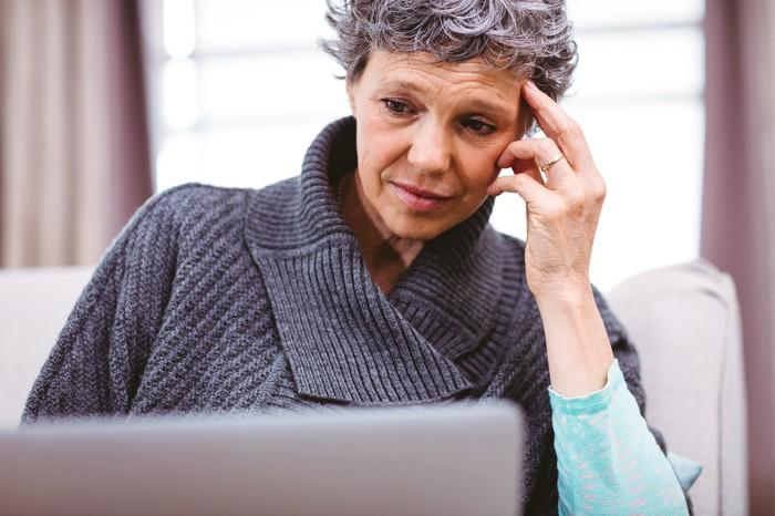 Older woman, with her hand on her temple, looking at her laptop.