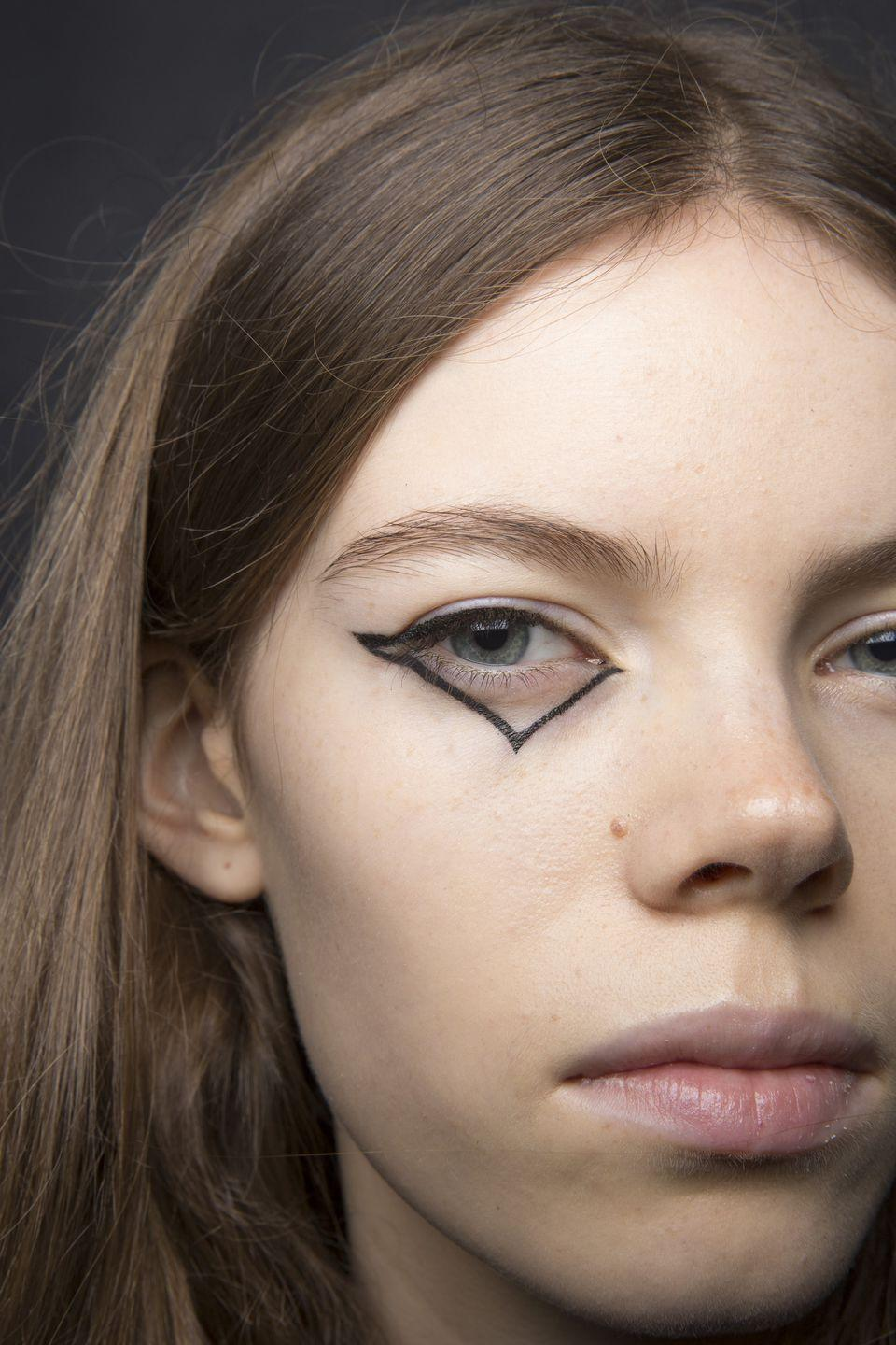 <p>Eyeliner took a downward turn (in a good way!) at Coach's spring show. A handful of models walked the runway wearing a cat-eye that continued along the lower lashline and down into a triangle.</p>