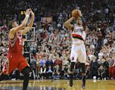 Portland Trail Blazers' Damian Lillard (0) shoots his winning shot against the Houston Rockets during the last .9 of a second of game six of an NBA basketball first-round playoff series game in Portland, Ore., Friday May 2, 2014. The Trail Blazers won the series in a 99-98 win. (AP Photo/Greg Wahl-Stephens)