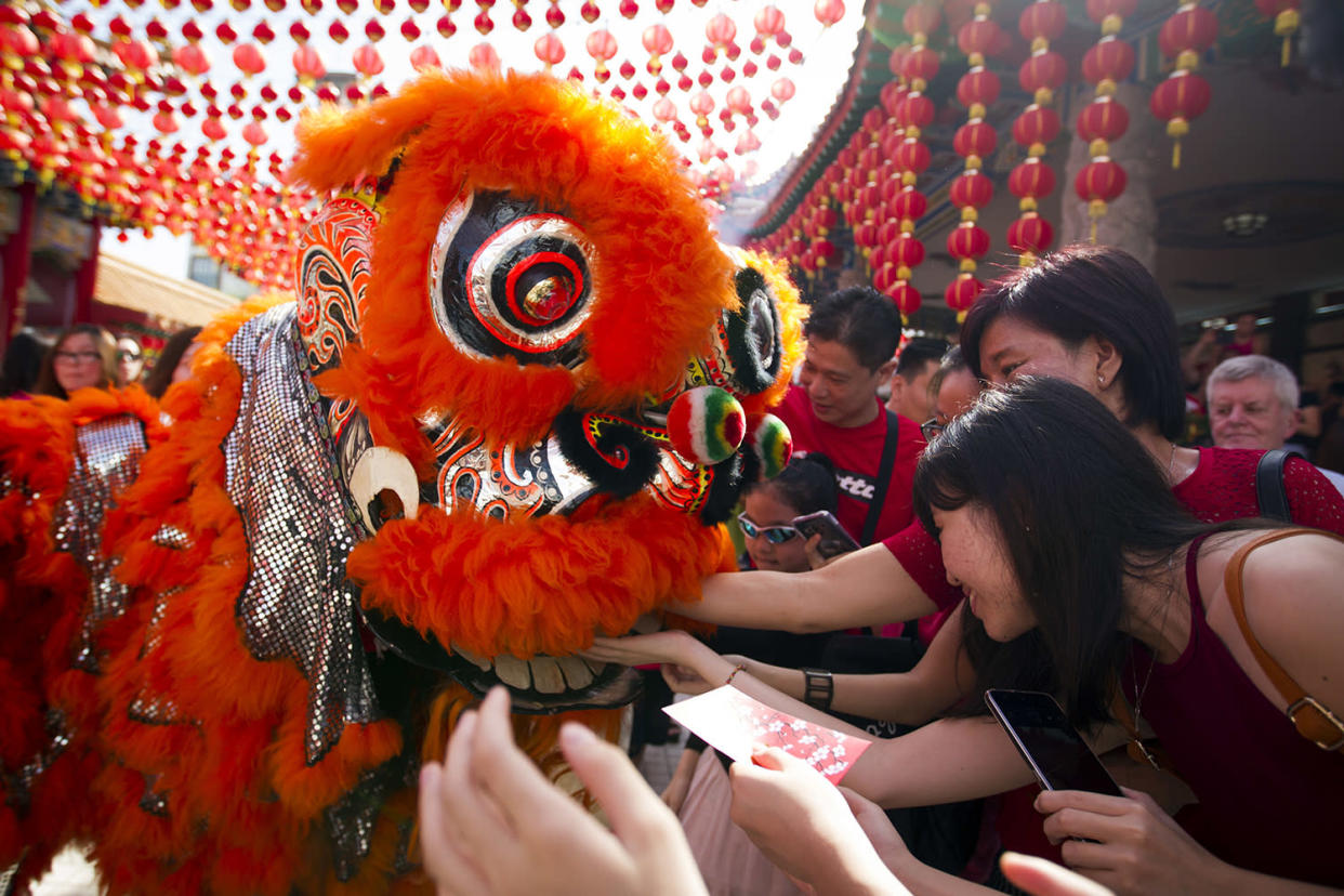 Temple visitors give red packets to the lion dance troupe during the lion dance performance on the first day of Chinese Lunar New Year at a temple in Kuala Lumpur, Malaysia, Saturday, Jan. 28, 2017. The celebration marks the Year of the Rooster in the Chinese calendar. (AP Photo/Lim Huey Teng)
