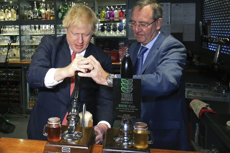 Britain's Prime Minister Boris Johnson pulls a pint with newly elected Conservative party MP for Sedgefield, Paul Howell at Sedgefield Cricket Club in County Durham, north east England, Saturday Dec. 14, 2019, following his Conservative party's general election victory.  Johnson called on Britons to put years of bitter divisions over the country's EU membership behind them as he vowed to use his resounding election victory to finally deliver Brexit. (Lindsey Parnaby/Pool via AP)